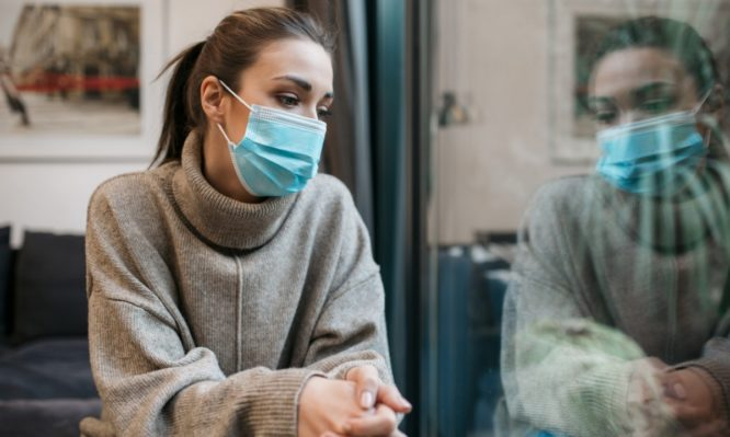 beautiful-woman-sitting-at-home-wearing-a-protective-face-mask-picture-id1293320477-666x399-1